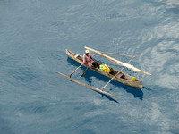 Man selling fruit from outrigger canoe.
