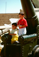 Two young boys play on cannon