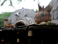 Thatched roof decorated with skull and pots.